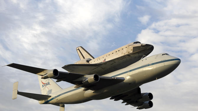 Space shuttle Endeavour, bolted atop a modified jumbo jet, makes its departure from the Kennedy Space Center, Wednesday, Sept. 19, 2012, in Cape Canaveral, Fla. Endeavour will make a stop in Houston before heading to the California Science Center in Los Angeles.(AP Photo/Terry Renna)