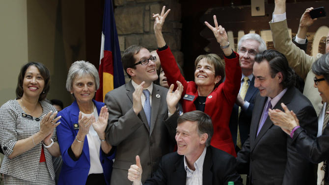 Colorado Gov. John Hickenlooper gives a thumbs up as he celebrates with members of the legislature after he signs the Civil Unions Act into law at the Colorado History Museum in Denver, Colo., on Thursday, March 21, 2013. (AP Photo/Brennan Linsley)