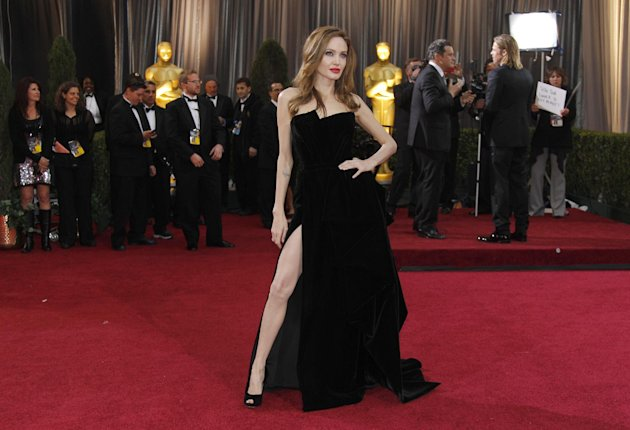FILE - This Feb. 26, 2012 file photo shows Angelina Jolie posing before the 84th Academy Awards in the Hollywood section of Los Angeles. Every year fashion offers up the good, the bad and the ugly. But what the industry is really built on _ and consumers respond to _ is buzz. Jolie&#39;s leg, that peeked out of the high thigh-high slit of her Versace gown, was the most exciting appearance on the red carpet. (AP Photo/Amy Sancetta, file)