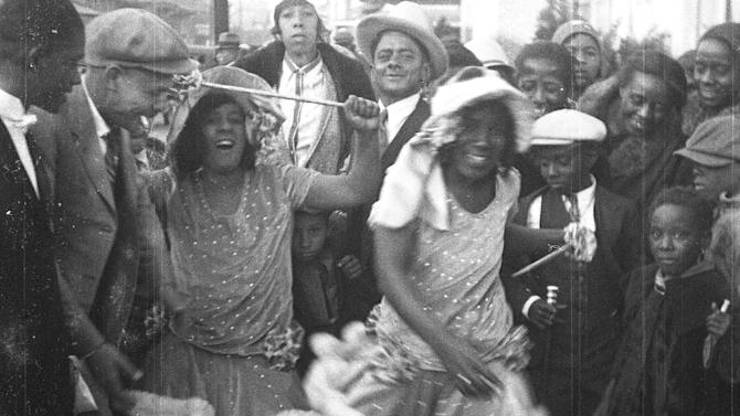 "This still frame from a film strip provided by Story Sloan Gallery shows women dressed as ""baby dolls"" dancing on a New Orleans street at Mardi Gras in 1931. The first known group of women to strut and dance in short ""baby doll"" dresses was a group of African-American prostitutes who wanted to outdo another group in 1912, but the style soon spread to respectable black neighborhoods and is seeing a modern revival. (AP Photo/Story Sloan Gallery)"