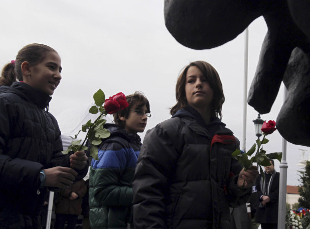 Children place flowers at the Holocaust Memorial commemorating the persecution of the Jewish people during World War II, in Thessaloniki, northern Greece, on Sunday, Jan. 27, 2013. There were some 50,