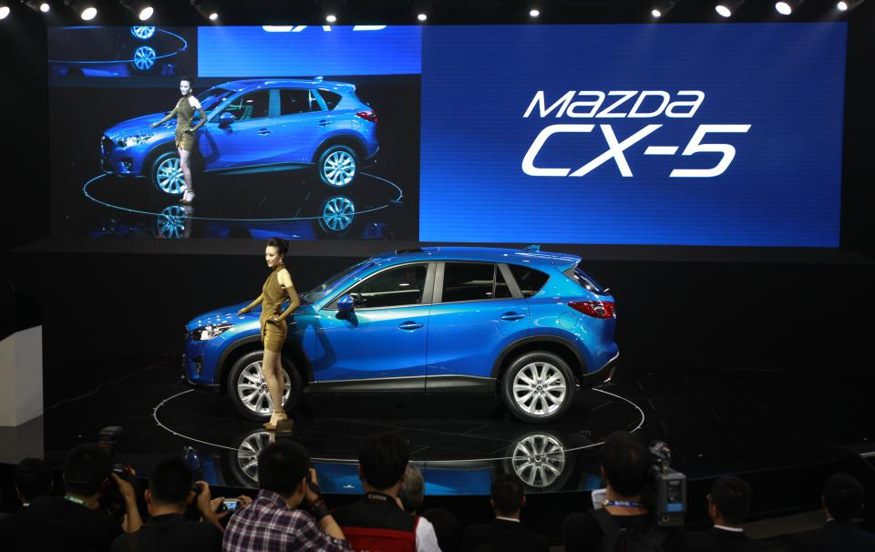 A model poses with Mazda's newly launched SUV CX-5 at the Beijing International Auto Exhibition in Beijing, China, Monday, April 23, 2012.  (AP Photo/ Vincent Thian)