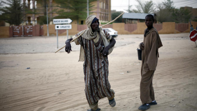 Men walk in Timbuktu, Mali, Friday Feb. 1, 2013. French President Francois Hollande is scheduled to arrive in Timbuktu Saturday for a short visit.(AP Photo/Jerome Delay)