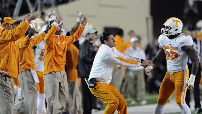 Tennessee head coach Derek Dooley, second from right, pulls linebacker Jacques Smith off the field during an NCAA college football game against Vanderbilt at Vanderbilt Stadium in Nashville , Saturday, Nov. 17, 2012. (AP Photo/Knoxville News Sentinel, Amy Smotherman Burgess)
