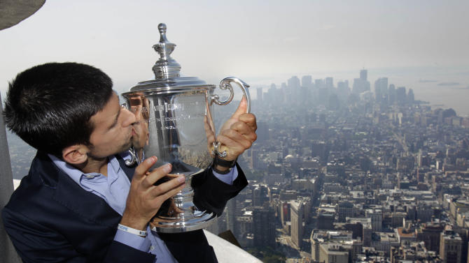 Novak Djokovic, of Serbia, poses with his U.S. Open trophy at the top of the Empire State Building in New York, Tuesday Sept. 13, 2011. Djokovic defeated Rafael Nadal Sunday to win his first U.S. Open tennis championship and third Grand Slam trophy of the year. (AP Photo/Seth Wenig)