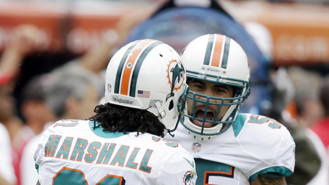 Miami Dolphins outside linebacker Koa Misi (55) congratulates cornerback Richard Marshall (31) after Marshall intercepted a pass from New York Jets Mark Sanchez during the first half of an NFL football game on Sunday, Sept. 23, 2012, in Miami. (AP Photo/Lynne Sladky)