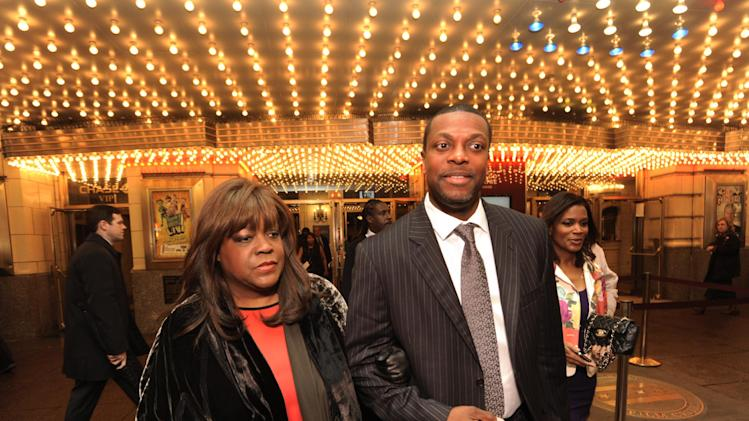 Roger Ebert's wife Chaz Ebert, left, and actor Chris Tucker, right, walk outside The Chicago Theater to look at the marquee before a memorial for film critic Roger Ebert in Chicago, Thursday, April 11, 2013. The Pulitzer Prize winning critic died last week at the age of 70 after a long battle with cancer. (AP Photo/Paul Beaty)