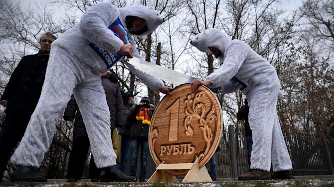Supporters of Russia's Communist Party dressed as white bears, the symbol of pro-presidential United Russia party, saw a model of a one ruble coin in half during a rally to protest the fall of the currency in Moscow on December 22, 2014