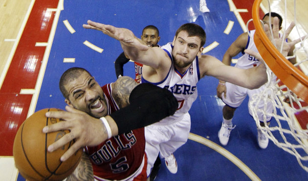 Chicago Bulls' Carlos Boozer (5) shoots as Philadelphia 76ers' Spencer Hawes defends in the first half of Game 6 in an NBA basketball first-round playoff series, Thursday, May 10, 2012, in Philadelphia. (AP Photo/Matt Slocum)