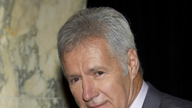 "FILE - In a May 21, 2012, file photo, honoree Alex Trebek, host of the game show ""Jeopardy"" holds a  71st Annual Peabody Awards in New York. Trebek received a Peabody Award for electronic media, as ""Jeopardy!,"" joined other awardees including serious documentaries, edgy comedies and high-toned dramas. (AP Photo/Charles Sykes, File)"