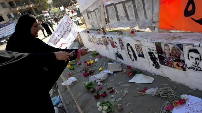 "Two Egyptian women protesters pay their respects in front of a spot designated for pictures of protesters killed during the Egyptian revolution and verses of Quran that reads ""do not kill the soul that God restricted you from killing without justice,"" at Tahrir Square, Cairo, Egypt, Friday, Dec. 7, 2012. Thousands of Egyptians took to the streets after Friday midday prayers in rival rallies and marches across Cairo, as the standoff deepened over what opponents call the Islamist president's power grab, raising the specter of more violence. (AP Photo/Nasser Nasser)"
