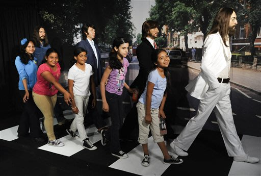 School children pose with wax figures representing The Beatles, from left, George Harrison, Paul McCartney, Ringo Starr and John Lennon are unveiled at Madame Tussauds New York, Thursday June 14, 2012