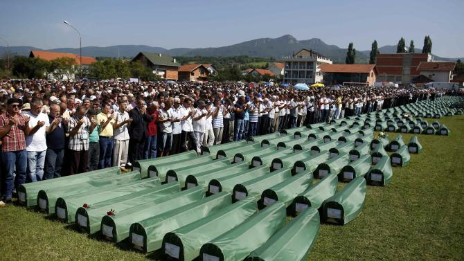Bosnian Muslims pray near the coffins of relatives during mass funeral for bodies found in a mass grave, in Kozarac