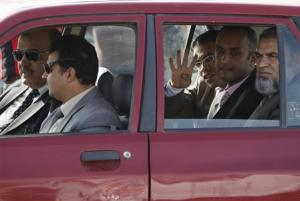 A lawyer of the Muslim Brotherhood and ousted Egyptian President Mohamed Mursi gestures with four fingers as he arrives at the police academy, before the start of Mursi's trial, on the outskirts of Cairo