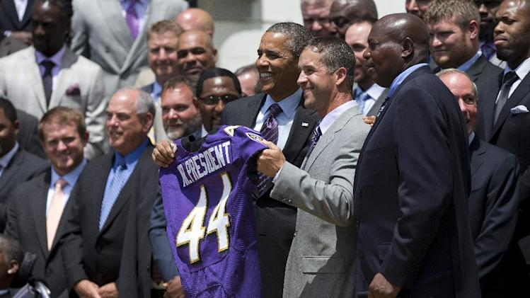 President Barack Obama and Baltimore Ravens head coach John Harbaugh, center, hold a Baltimore Ravens football jersey presented to the president during a ceremony on the South Lawn of the White House in Washington, Wednesday, June 5, 2013, where the president honored the Super Bowl XLVII champs. The Ravens defeated the San Francisco 49ers in Super Bowl XLVII. General Manager Ozzie Newsome is at right. (AP Photo/Evan Vucci)