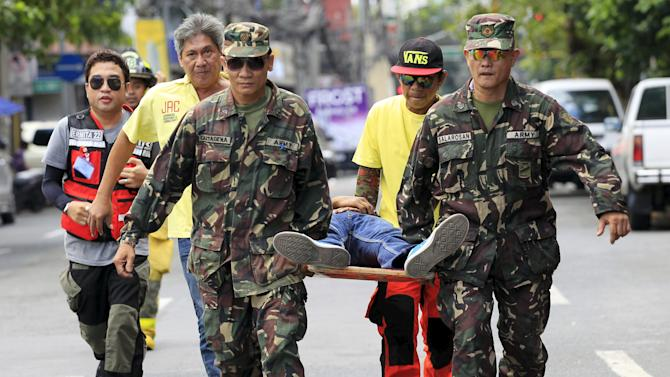 Soldiers help rescue volunteers carry a mock victim on a stretcher as they participate in the simultaneous earthquake drill in Manila