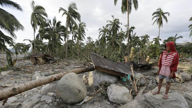 A resident looks at the devastation brought about by the flash flood that hit the village of Andap, New Bataan township, Compostela Valley in southern Philippines Wednesday Dec. 5, 2012. Typhoon Bopha, one of the strongest typhoons to hit the Philippines this year, barreled across the country's south on Tuesday, killing scores of people while triggering landslides, flooding and cutting off power in two entire provinces. (AP Photo/Bullit Marquez)