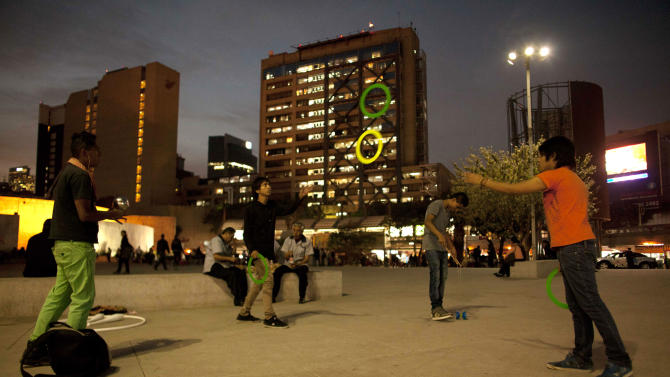 In this photo taken on Dec. 13, 2012, young men play catch with flying rings at the Glorieta de Insurgentes roundabout and metro station in Mexico City.  When the plaza was built in 1969, the city's top priority was moving an onslaught of cars and people from one point to another. The circular plaza is below ground to let pedestrians walk under busy thoroughfares to catch their trains or buses or to just hang out. Urban designers are seeking to transform the roundabout into something with the glitzy excitement of Times Square or Londonís Piccadilly Circus. (AP Photo/Alexandre Meneghini)