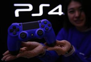 Staff at the PlayStation 4 launch event poses with PlayStation 4's game controller before its domestic launch event at the Sony Showroom in Tokyo