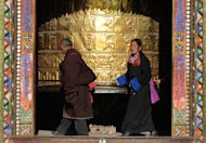 This file photo shows Tibetan pilgrims near a giant prayer wheel at the Rongwu monastery in Tongren, Qinghai Province, pictured on March 17, 2008. A Chinese court in a Tibetan area on Friday convicted a man of intentional homicide and inciting secession for &#39;goading&#39; a monk to set himself on fire, state media reported, even though the monk did not follow through