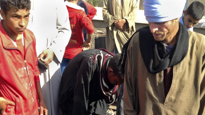 """Egyptians gather body parts at the scene of a train crash that killed at least 47 people, most of them children near Assiut  in southern Egypt, Saturday, Nov. 17, 2012. As one man picked up a body part he screamed: """"Only God can help!"""" The bus was carrying more than 50 children between 4 and 6 years old when it was hit near al-Mandara village in Manfaloot district in the province of Assiut, a security official said, adding that it appears that the railroad crossing was not closed as the train sped toward it. (AP Photo/Mamdouh Thabet)"""