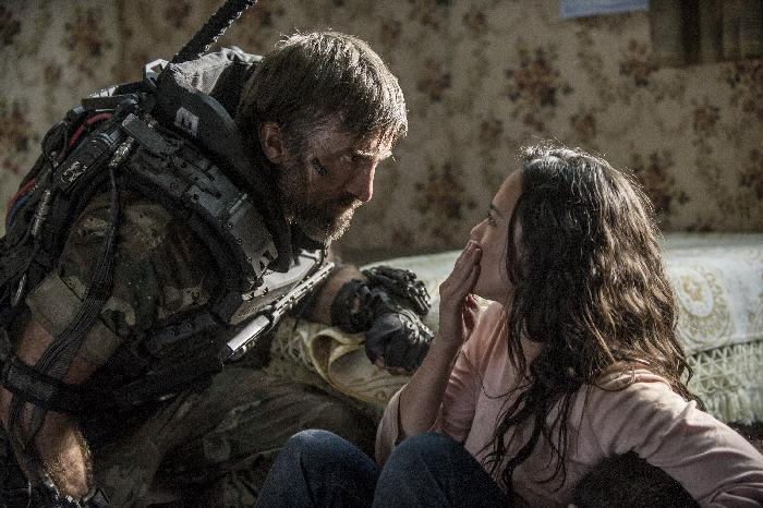 "This film publicity image released by TriStar, Columbia Pictures-Sony shows Sharlto Copley, left, and Alice Braga in a scene from ""Elysium."" (AP Photo/TriStar, Columbia Pictures - Sony, Kimberley French)"