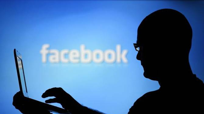 A man is silhouetted against a video screen with an Facebook logo as he poses with an Dell laptop in this photo illustration taken in the central Bosnian town of Zenica