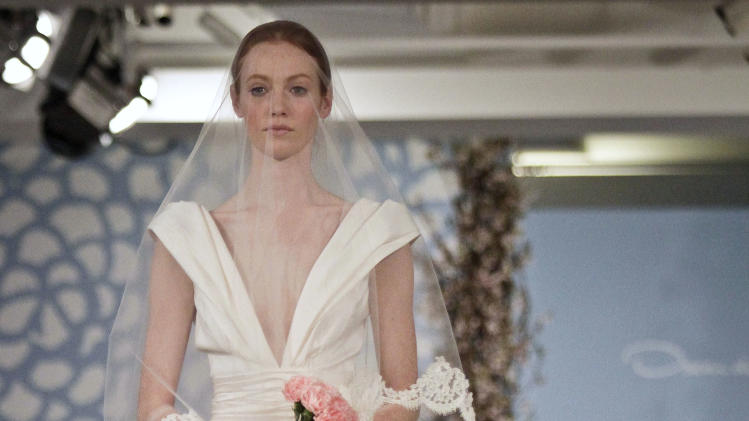 A model presents a bridal fashion creation from the Oscar de la Renta collection, in New York, Monday, April 22, 2013. (AP Photo/Bebeto Matthews)