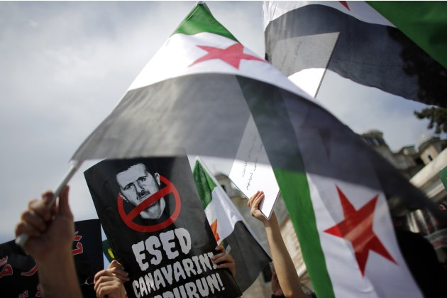 Demonstrators wave Syrian opposition flags during a protest against Syria's President Bashar al-Assad at the courtyard of Fatih mosque in Istanbul
