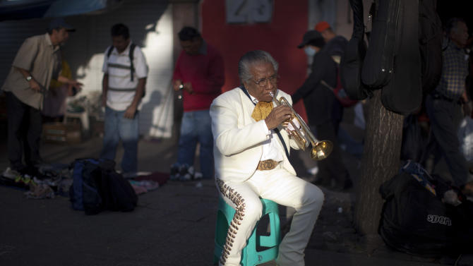 In this Oct. 5, 2012 photo photo, mariachi musician Jesus Velazquez practices his trumpet as he waits for clients at Plaza Garibaldi in Mexico City. The new Mariachi School Ollin Yoliztli in Mexico City is seeking to revive a music that's lost ground over the years. The school, whose name means life and movement in indigenous Nahautl, teaches folk bands how to play professionally while grooming a new generation of songwriters and composers.  (AP Photo/Alexandre Meneghini)
