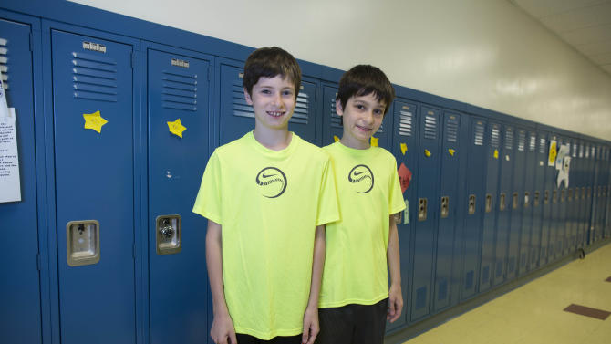 In this Thursday, June 6, 2013 photo, Luke Rogers, left, and his twin brother, Sam, one of the twenty-four sets of twins from Highcrest Middle School in Wilmette, Ill. pose for a portrait at the school. The group is attempting to break a Guinness World record for the amount of twins in one grade which is currently 16 sets. (AP Photo/Scott Eisen)