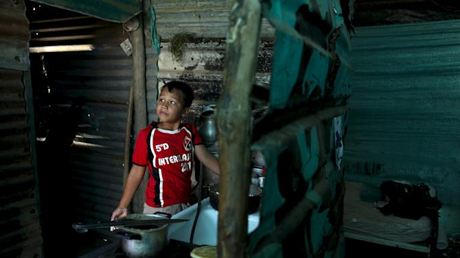 A kid helps her mom to cook breakfast at their house which has been marked for demolition, during a special deployment close to the border with Colombia, at San Antonio in Tachira state
