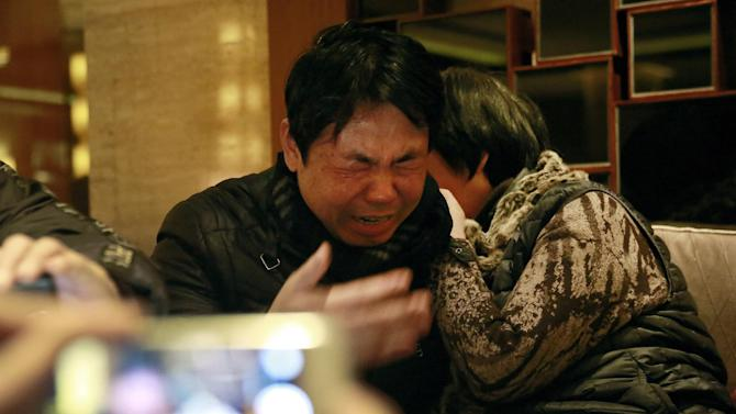 "Jiang Hui, left, and Dai Shuqin, relatives of passengers onboard the Malaysia Airlines Flight 370 that went missing on March 8, 2014, react while watching a laptop computer screen showing a pre-recorded message broadcast on Malaysian television by Malaysia's Civil Aviation Authority, in Beijing Thursday, Jan. 29, 2015. Malaysia's Civil Aviation Authority has officially declared the MH370 crash an accident, fulfilling a legal obligation that will allow efforts to proceed with compensation claims. Malaysia civil aviation chief Azharuddin Abdul Rahman said Thursday that the search for the Malaysia Airlines jet that disappeared on March 8, 2014, ""remains a priority."" (AP Photo/Andy Wong)"