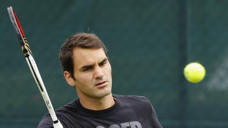 Roger Federer of Switzerland plays a return during a training session at the Wimbledon tennis championships in London, Sunday, June 23, 2013. The Championships start Monday, with defending men's champion Roger Federer of Switzerland attempting to win the title for the eighth time. (AP Photo/Kirsty Wigglesworth)