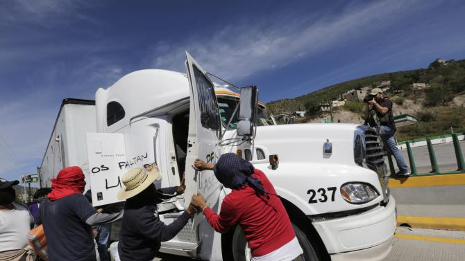 Masked CETEG members open the door of a federal police truck as they block the road to Acapulco on the outskirts of Chilpancingo