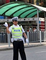 This file picture shows then-Chongqing police chief Wang Lijun directing traffic in order to set an example to his policemen in southwest China's Chongqing municipality, in 2010. Wang, Bo Xilai's former right-hand man, will go on trial in southwest China next week, a court said on Friday, the latest stage in a scandal that has rocked the Communist party ahead of a 10-yearly power handover