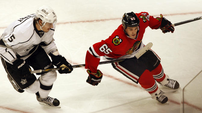 Los Angles Kings' Keaton Ellerby  (5) puts a stick on Blackhawks' Andrew Shaw (65) in the second period of an NHL hockey game on Sunday, Feb. 17, 2013, in Chicago. The Blackhawks  won 3-2. (AP Photo/John Smierciak)