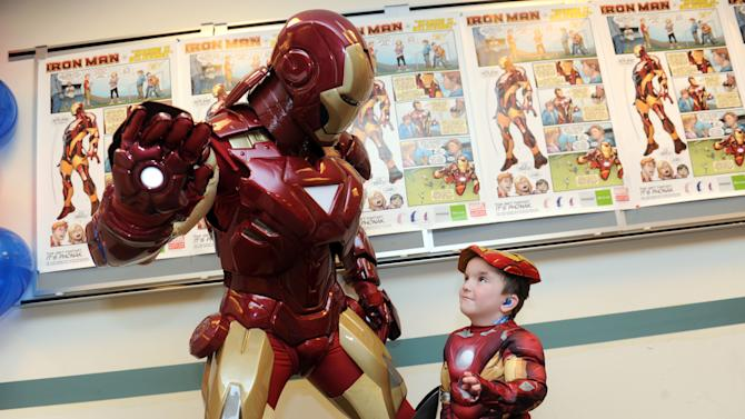 IMAGE DISTRIBUTED FOR PHONAK - Phonak hearing aid wearer Anthony Smith, 5, of Salem, NH, greets Marvel's Iron Man, Tuesday, Feb. 26, 2013, in New York, during an event to announce a unique partnership between Phonak and Marvel Custom Solutions to produce an educational poster geared for children that highlights the benefits of hearing aids.   (Photo by Diane Bondareff/Invision for Phonak/AP Images)