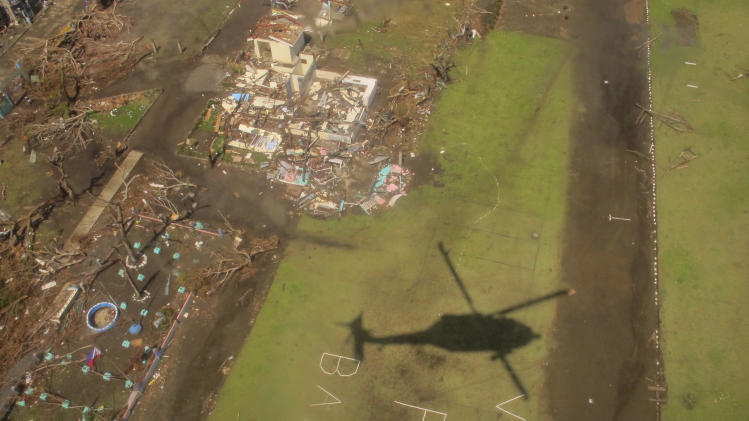 In this photo taken Saturday, Nov. 16, 2013, the shadow of a U.S. military helicopter on a disaster relief mission is cast passing over a sign pleading for help near Tacloban, Philippines. The U.S. military has launched a massive relief effort for victims of Typhoon Haiyan in an effort to both save lives and build relations with its allies around the region by showing that it has the military strength to provide support in times of need. (AP Photo/Eric Talmadge)