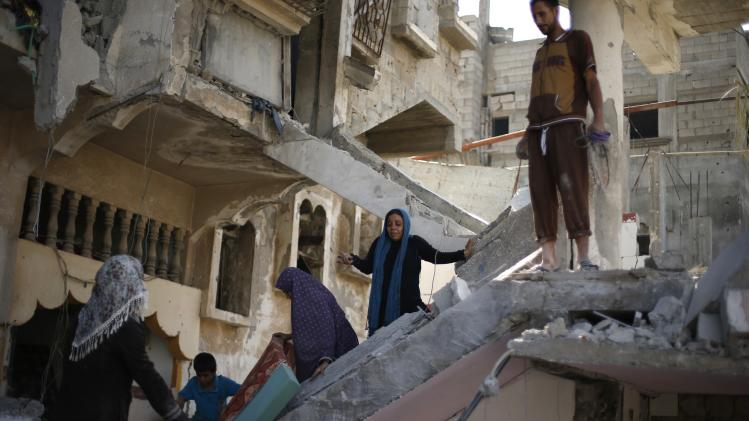A Palestinian woman reacts upon seeing the wreckage of her house in Beit Hanoun town