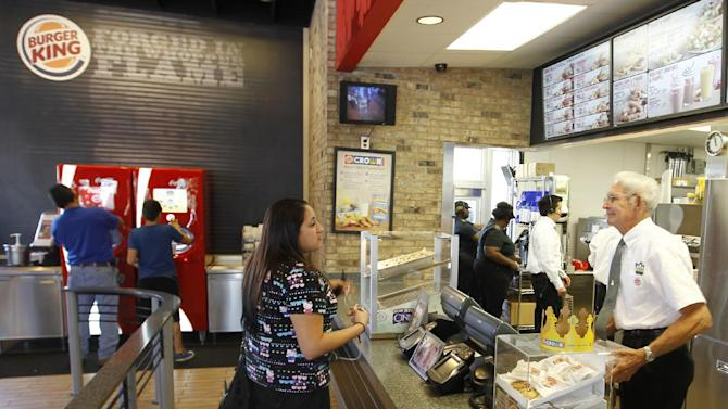 In this March 28, 2012 photo, Jenny Vega orders food at a Burger King restaurant in Miami. Burger King launches 10 menu items including smoothies, frappes, specialty salads and snack wraps in a star-studded TV ad campaign. It's the biggest menu expansion since the chain opened its doors in 1954. (AP Photo/Luis M. Alvarez)