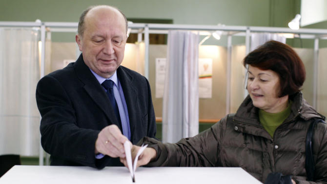 Lithuania's Prime Minister and Homeland Union leader Andrius Kubilius, left, and his wife Rasa vote at a polling station in Vilnius, Lithuania, Sunday, Oct. 28, 2012. Lithuanians balloted Sunday in a second round of parliamentary elections. (AP Photo/Mindaugas Kulbis)