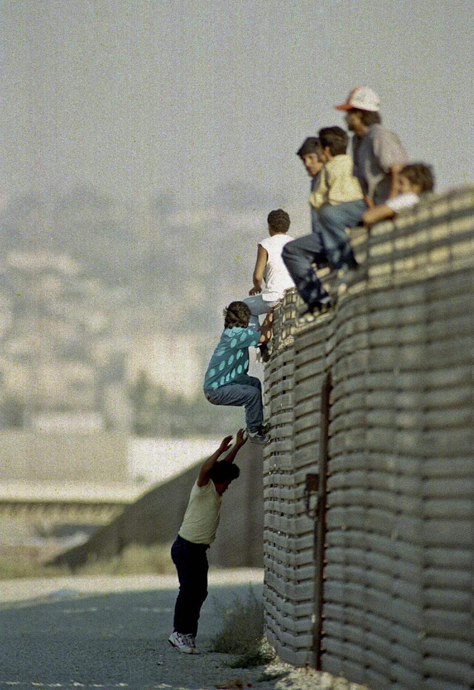 FILE - In this Oct. 14 1991 file photo, a group of illegal Mexican immigrants jump from a border fence to enter the United States, near Tijuana, Mexico. With new fencing and tougher enforcement the 1,954-mile border with Mexico is more difficult to breach than ever. (AP Photo/Lenny Ignelzi)
