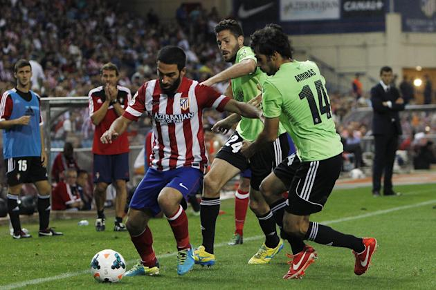 Atletico de Madrid's Arda Turan from Turkey, left, in action with Osasuna's Alejandro Arribas, right, and Damia Abella, centre, during a Spanish La Liga soccer match at the Vicente Calderon stadium in