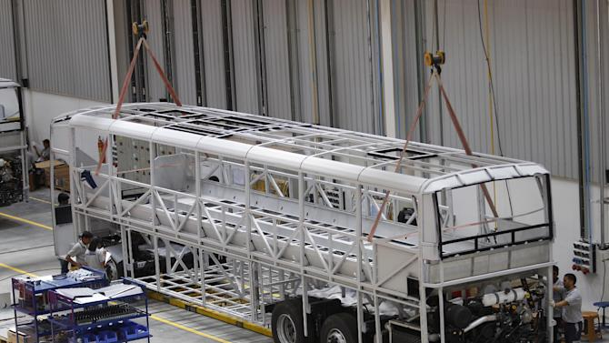 Indian employees of Scania work on a chassis of a bus at the company's new manufacturing facility in Narasapura, some 50 Kilometers (31 Miles) northeast of Bangalore, India, Monday, March 30, 2015. The Swedish commercial vehicle company announced the inauguration of its bus manufacturing facility Monday. The plant, which has a capacity of making about 1,000 units per year, shall be serving the Indian market and becoming a hub for exports to other markets in Asia, a company release said.(AP Photo/Aijaz Rahi)