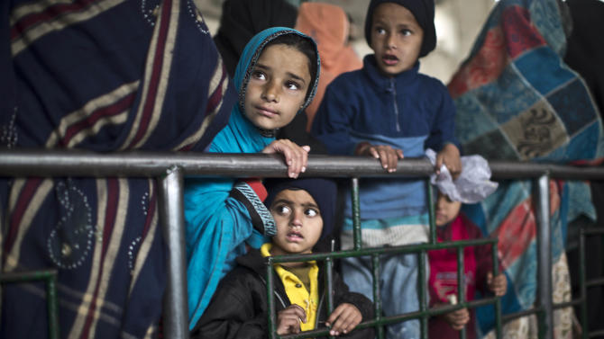Pakistani children wait for food donations at a distribution center in a shrine in Islamabad, Pakistan, Monday, Dec. 22, 2014. (AP Photo/Muhammed Muheisen)