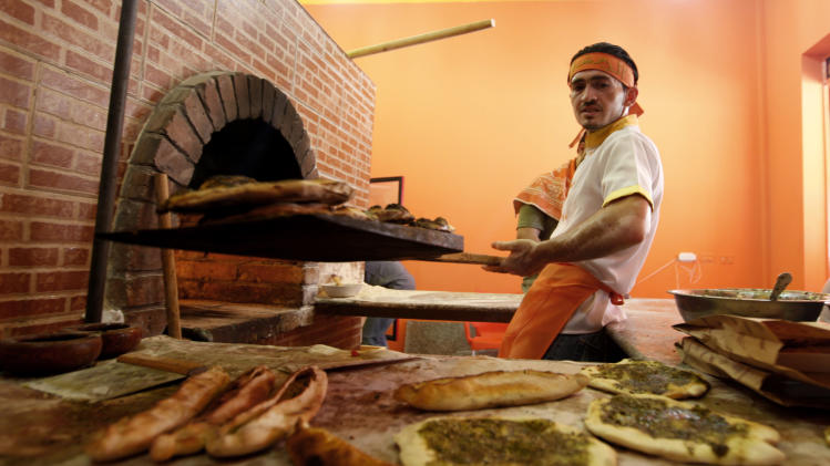 "In this Tuesday, June 11, 2013 photo, an employee works at ""Damashki"" or ""The Guy From Damascus"" bakery co-owned by Bassel Shunar, a Palestinian by origin who was born in Syria but who fled the country and arrived in the Gaza Strip two months ago. The civil war in Syria is increasingly hurting Hamas-ruled Gaza financially, according to several officials in the Islamic militant group and in Islamic charities. (AP Photo/Hatem Moussa)"