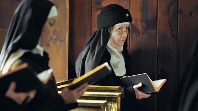 In this Thursday, Dec. 22, 2011 photo, Mother Dolores Hart, right, participates in two of seven daily prayers in the Abbey of Regina Laudis monastery in Bethlehem, Conn. Mother Dolores, a cloistered nun whose luminous blue eyes entranced Elvis Presley in his first on-screen movie kiss, is praying for a Christmas miracle. She walked away from Hollywood stardom in 1963 to become a nun in rural Bethlehem. Now she finds herself back in the spotlight, but this time it's all about serving the King of Kings, not smooching the King of Rock and Roll. The former brass factory that houses Mother Dolores and about 40 other nuns cloistered at the Abbey of Regina Laudis needs millions of dollars in renovations to meet fire and safety codes, add an elevator and make handicap accessibility upgrades. (AP Photo/Jessica Hill)