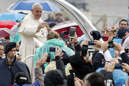Pope Francis waves to the faithful as he arrives to lead his weekly audience in Saint Peter's Square at the Vatican