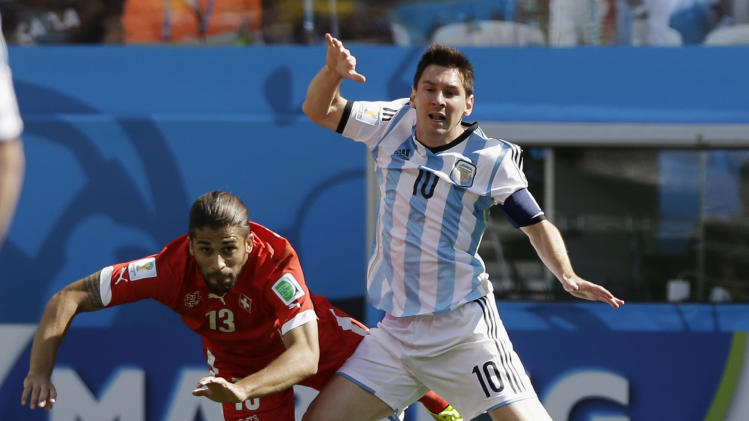 Argentina's Lionel Messi, right, fights for the ball with Switzerland's Ricardo Rodriguez during their World Cup round of 16 soccer match at the Itaquerao Stadium in Sao Paulo, Brazil, Tuesday, July 1, 2014